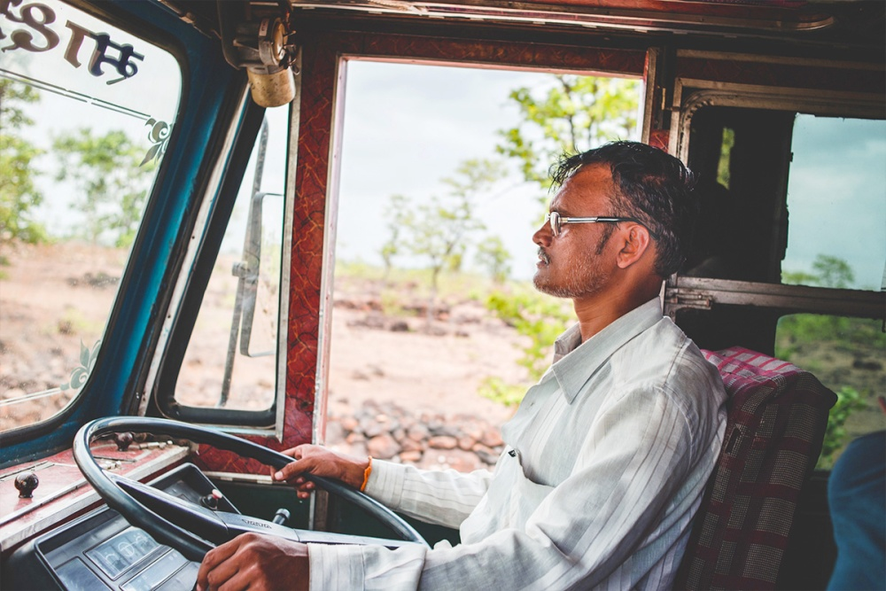 A truck driver in his multi-coloured truck enroute Jawhar Maharashtra India